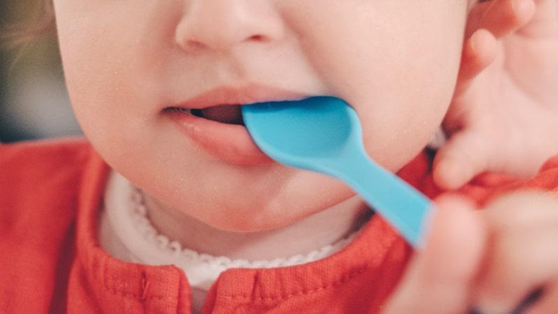 Bebé con una cuchara en la boca
