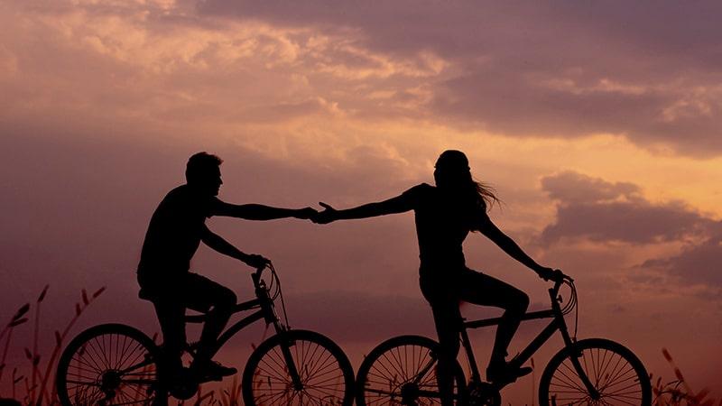 Pareja se da la mano en bici